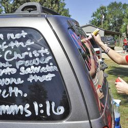 Kountze High School cheerleader Brooke Coates paints scripture verses on a car Wednesday, Sept. 19, 2012 in Kountze, Texas.  The small Hardin County community is rallying behind the high school's cheerleaders after the squad members were told they could not use scripture verses on their signs at the football games. (AP Photo/The Beaumont Enterprise, Dave Ryan)