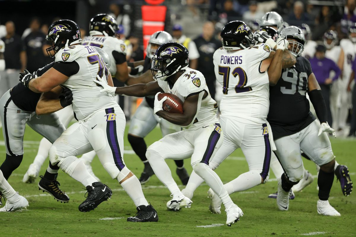 Running back Ty'Son Williams #34 of the Baltimore Ravens runs behind offensive guards Kevin Zeitler #70 and Ben Powers #72 against the Las Vegas Raiders during their game at Allegiant Stadium on September 13, 2021 in Las Vegas, Nevada.