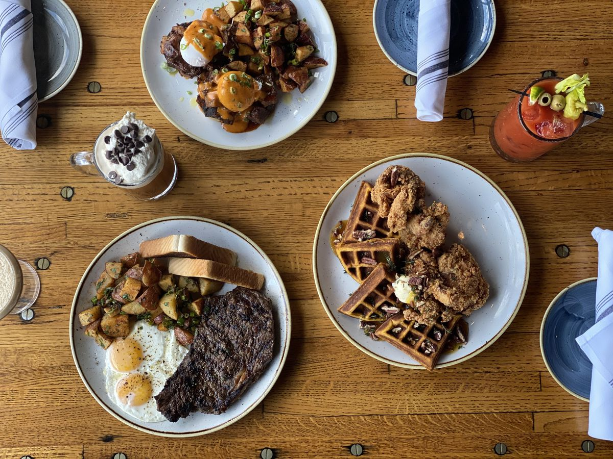 Overhead view of a wooden table covered with several dishes of brunch food and cocktails