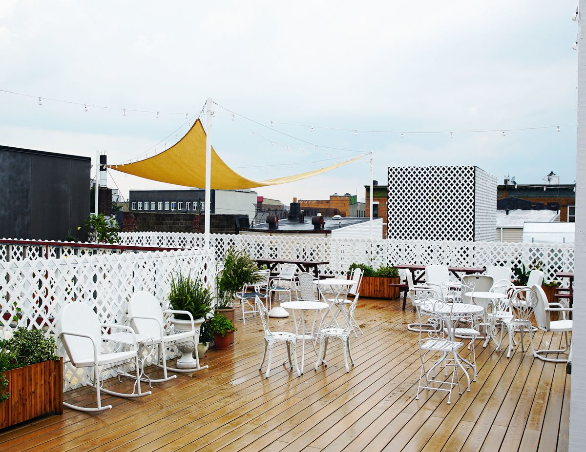 White chairs and tables are arranged on a rooftop deck slick with rain