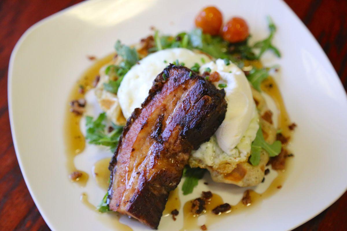 Praise the Lard braised pork belly over a poached egg on a lardon herb waffle