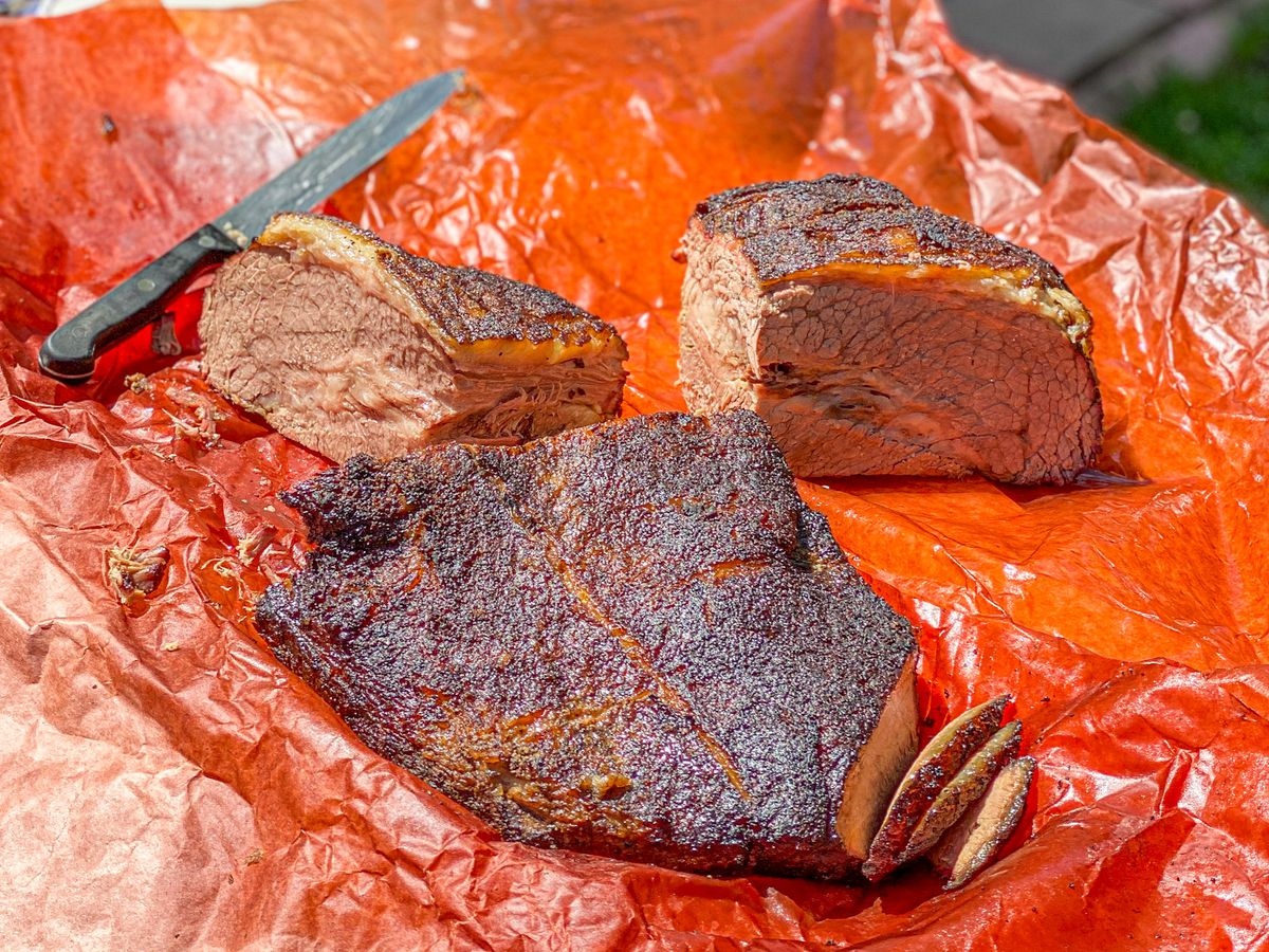A cut of brisket in red paper wrapping with knife for slicing.