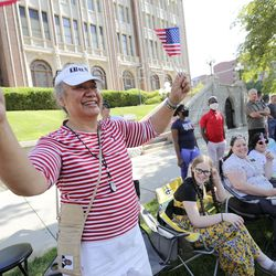 Mele Takuvaka waves flags and cheers as she watches the Days of '47 Parade in Salt Lake City on Friday, July 23, 2021.