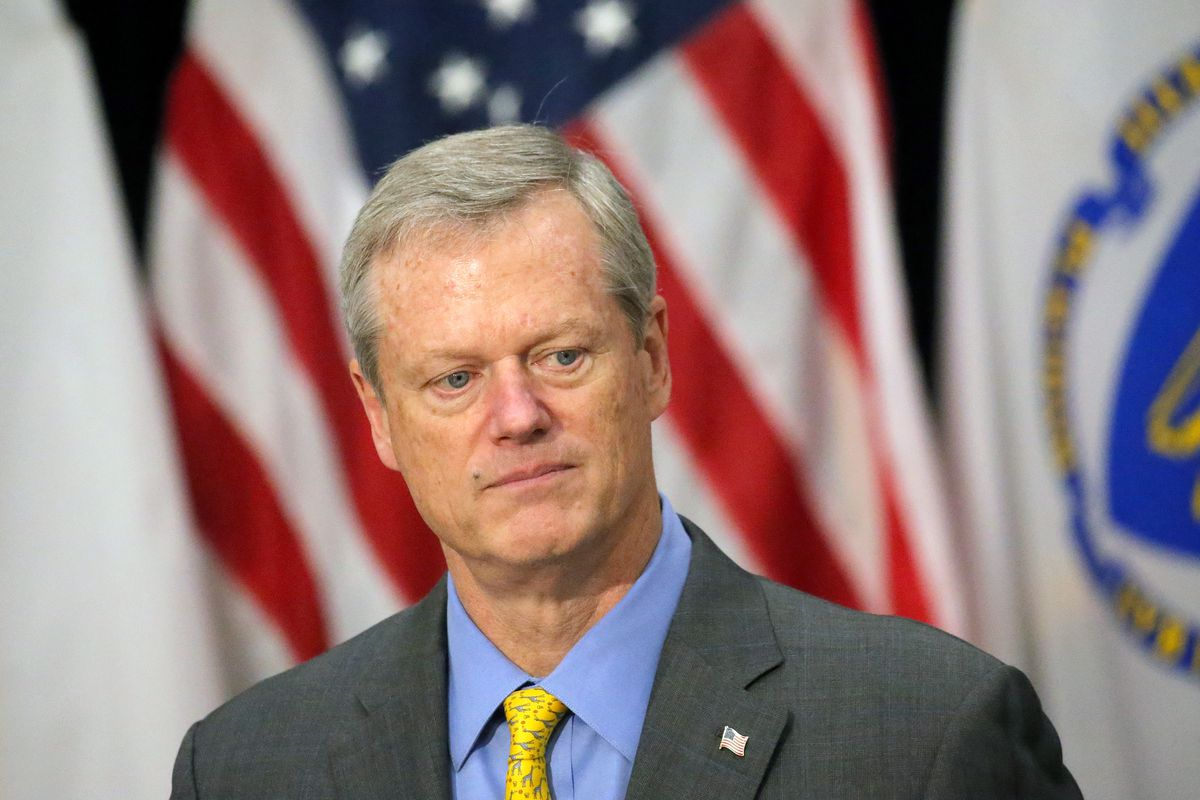 Closeup of Massachusetts Governor Charlie Baker at a press conference, wearing a suit and standing in front of the American flag and the Massachusetts flag