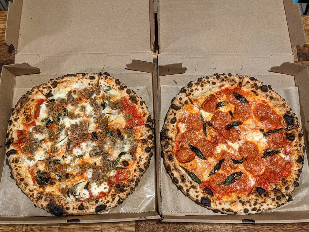 overhead view of two Neapolitan-style pizzas in pizza boxes, with leopard-spotted crusts and meat toppings