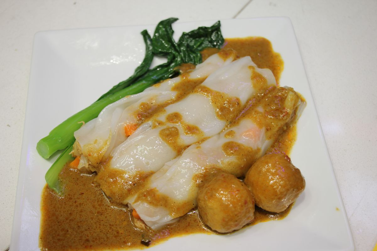 Three slender white rolls placed on a plate with brownish sauce and ball-shaped food next to it