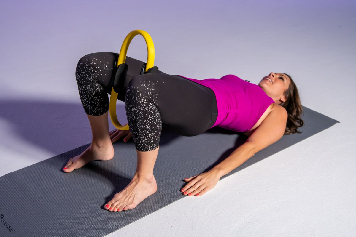 Adding a bridge adds an extra challenge to a pilates ring inner thigh exercise.