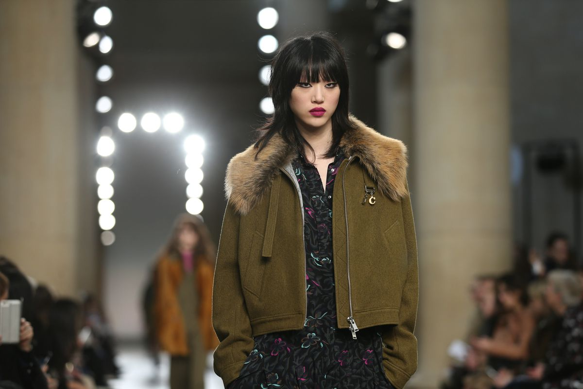 A model walks the runway at Topshop Unique's fall 2016 show wearing an army green jacket with fur trim.