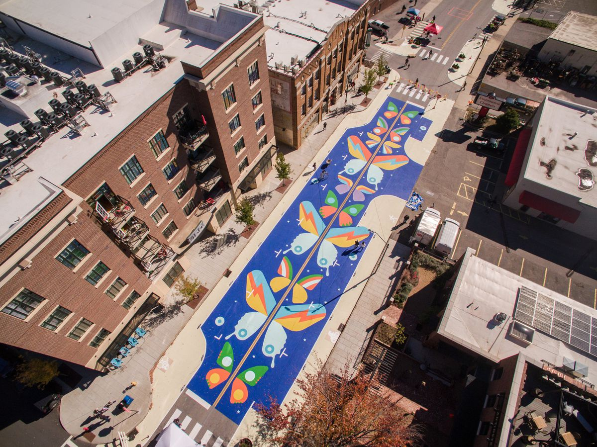 An aerial shot of a downtown street covered with brightly colored painted butterflies and sidewalk plazas.