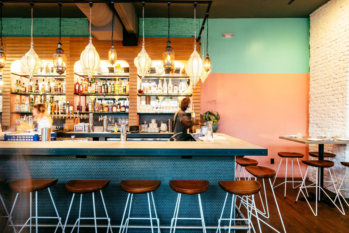 Bar with blue and pink walls and Moroccan-style light fixtures