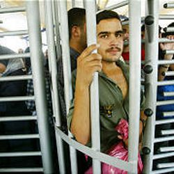 Palestinians wait to enter Israel. Iron turnstiles, holding pens are part of the latest checkpoint upgrades.