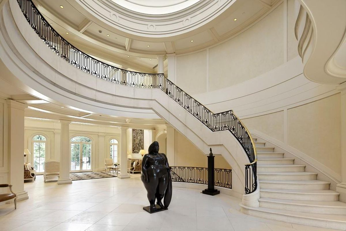 A mansion's grand entry foyer with a winding marble staircase and a statue in the middle of the foyer.