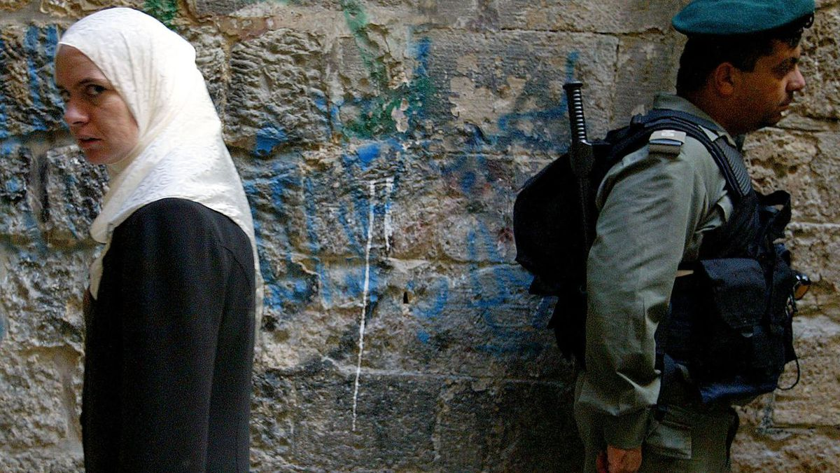 A Palestinian woman walks past an Israeli soldier outside the al-Aqsa Mosque in Jerusalem (Uriel Sinai/Getty Images)