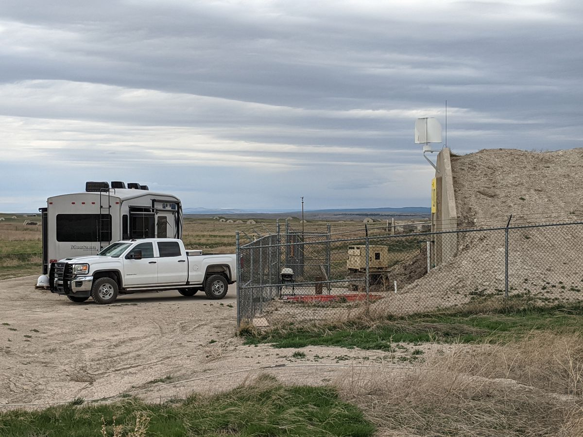 A photo of a white truck and tan camper van parked outside a bunker surrounded by a wire fence.