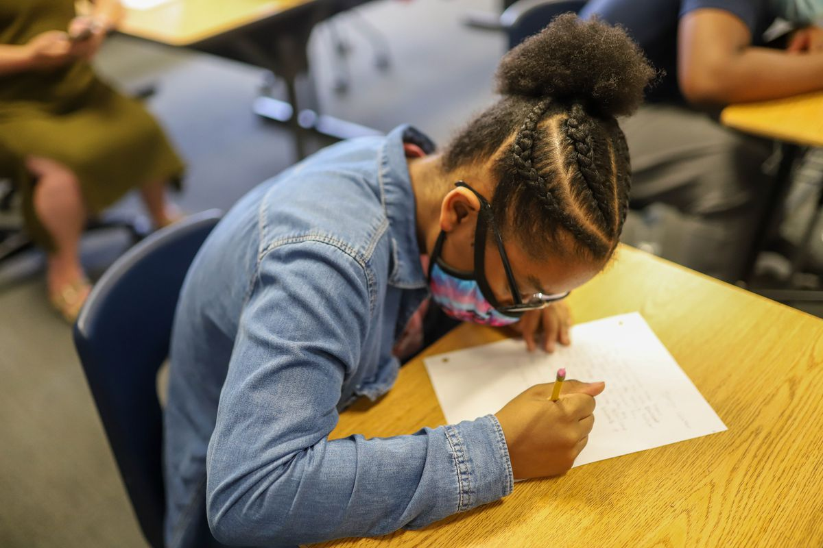 A student wearing a jean jacket and protective mask writes on a piece of notebook paper at her desk.