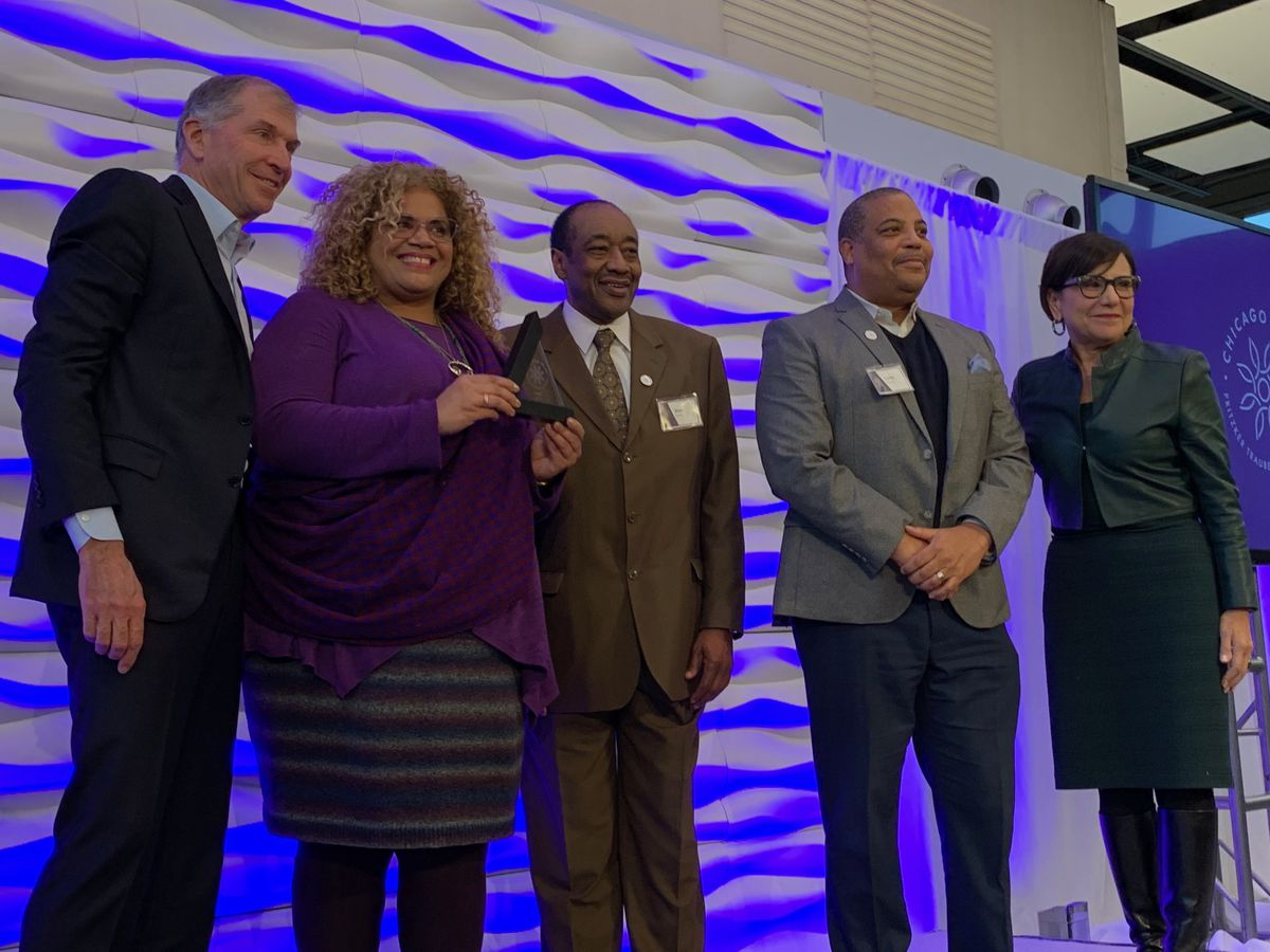 The Auburn-Gresham community development team accepts its Chicago Prize Challenge finalist award from Bryan Traubert and Penny Pritzker of the Pritzker Traubert Foundation on Wednesday.