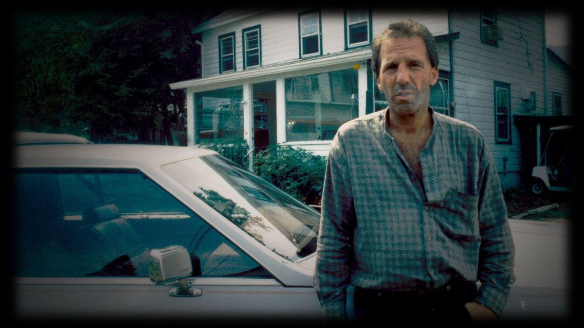 A man leans against a car, looking at the camera, in an image from Narrowsburg.