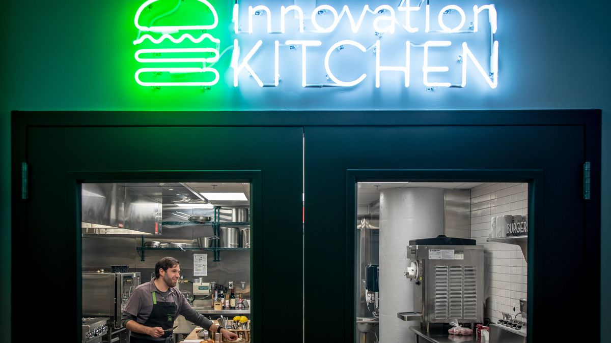 A bright neon sign signaling Shake Shack's Innovation Kitchen