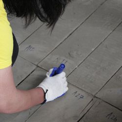 As part of a missionary service project, Sister Adelaide Tehei from Wapirobay, Gisborne, New Zealand, labels floor board of low income housing unit. Missionaries from the Sendai Japan Mission shoveled sludge from the foundation of the homes before the floor boards were reinstalled.