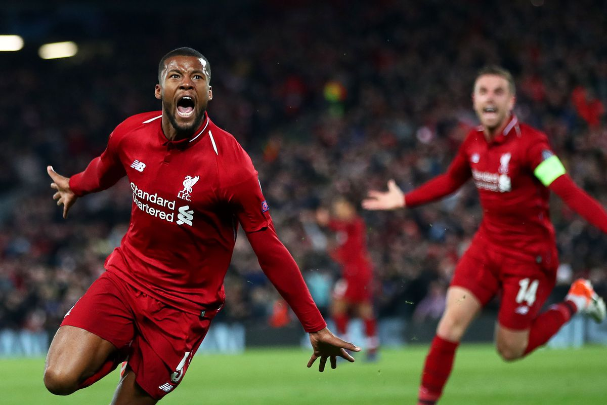 Gini Wijnaldum celebrates scoring the third goal against Barcelona in the comeback at Anfield in 2019. The Dutchman screams, running to the fans, hitting the badge on his chest. Captain Jordan Henderson is visible celebrating in his wake.