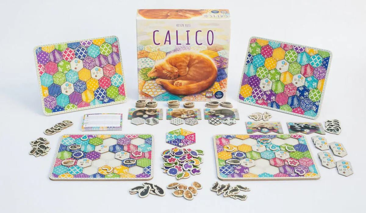 The components for knitting game Calico spread out on the table, including four player boards and five sleepy kitties.