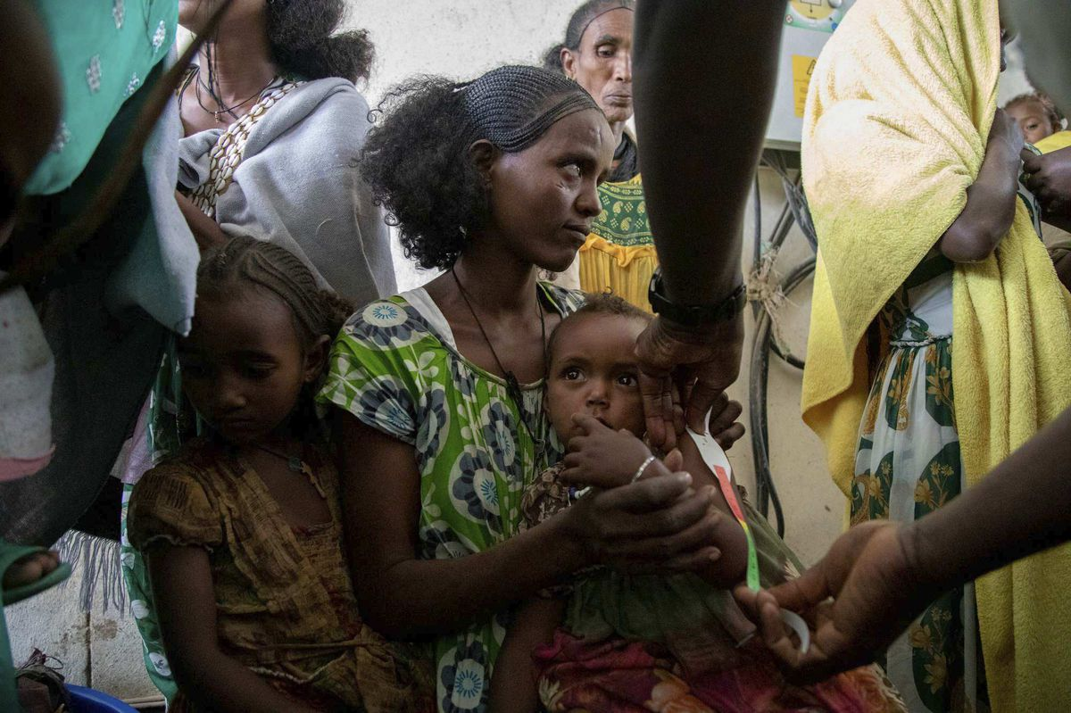 A woman holds a child during a screening for malnutrition in pregnant and lactating women by UNICEF and partners in Gijet in the Tigray region of northern Ethiopia.