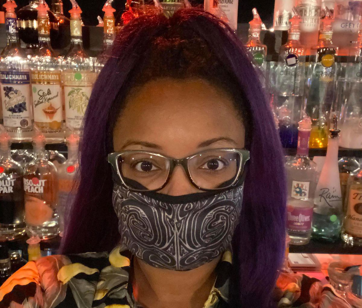 Melanie Mack wears glasses and a black and white printed mask in front of liquor bottles at the bar.