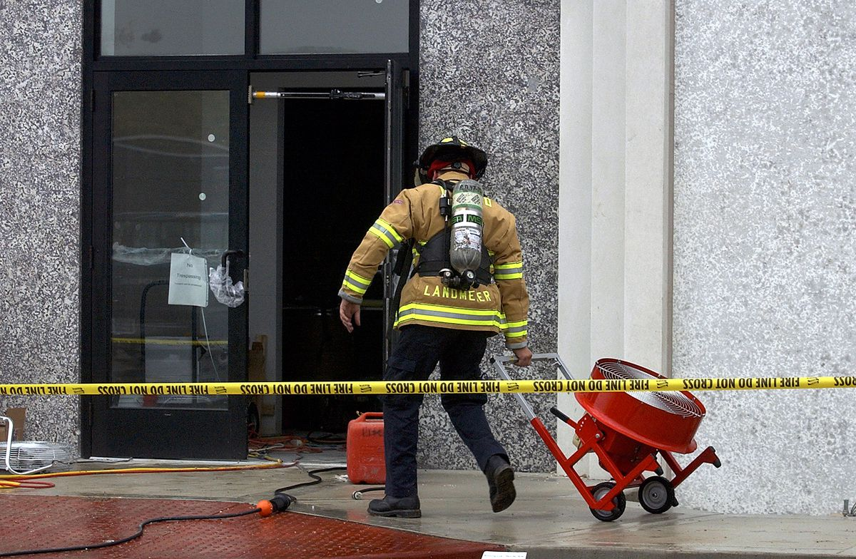 A firefighter is pulling a dolly with a fan that he will place inside a building in West Dundee after carbon monoxide from a generator sickened nine construction workers and a project manager in 2004.