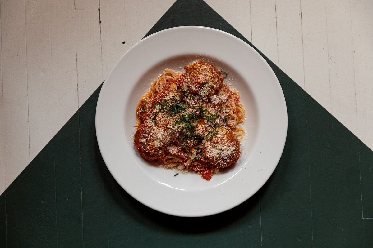 A white plate with spaghetti is topped with three large meatballs, red sauce, a dusting of parmesan, and chopped basil.
