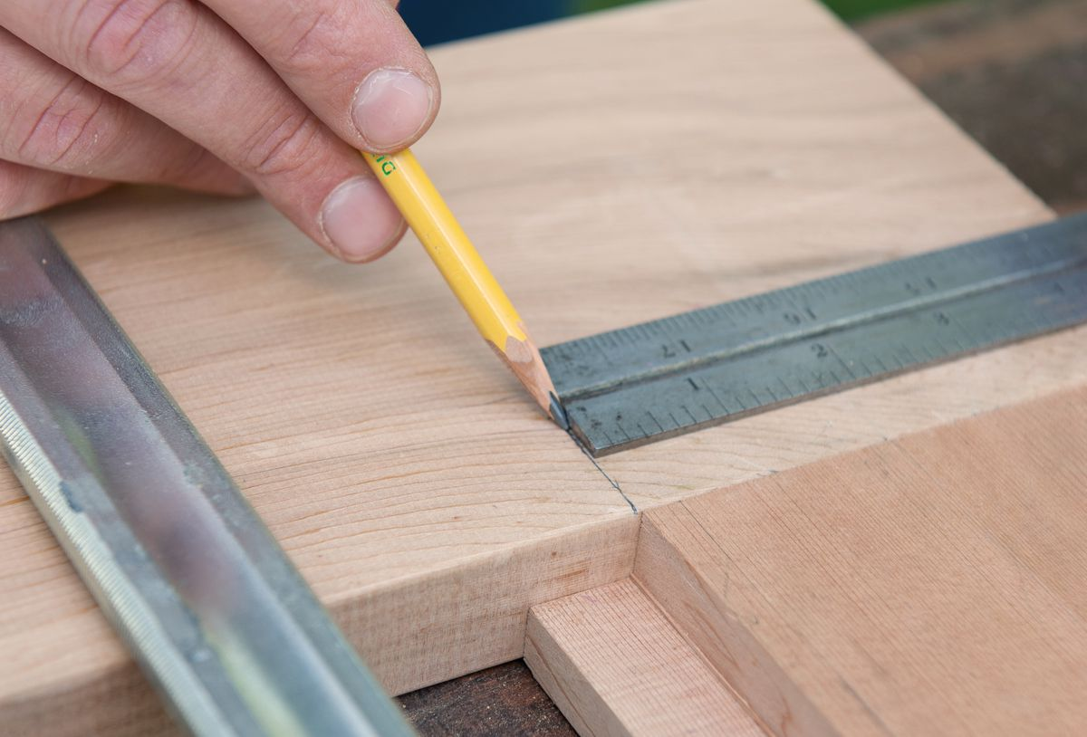 Man Draws Registration Marks With Combination Square For Picnic Table