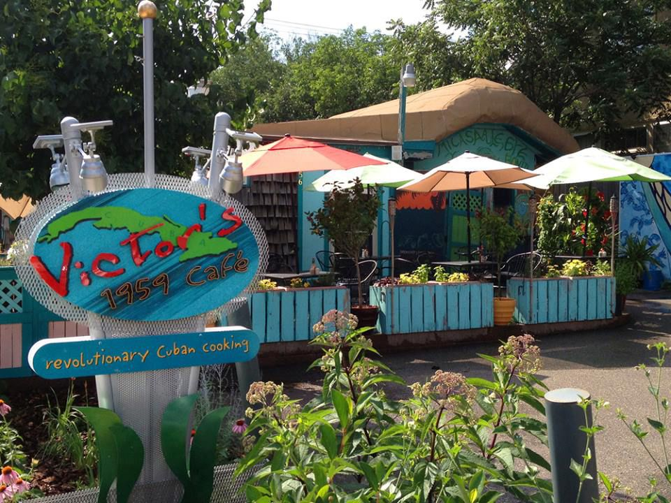 The vibrant exterior of Victor's is filled with tropical colors and flowers on a sunny summer day