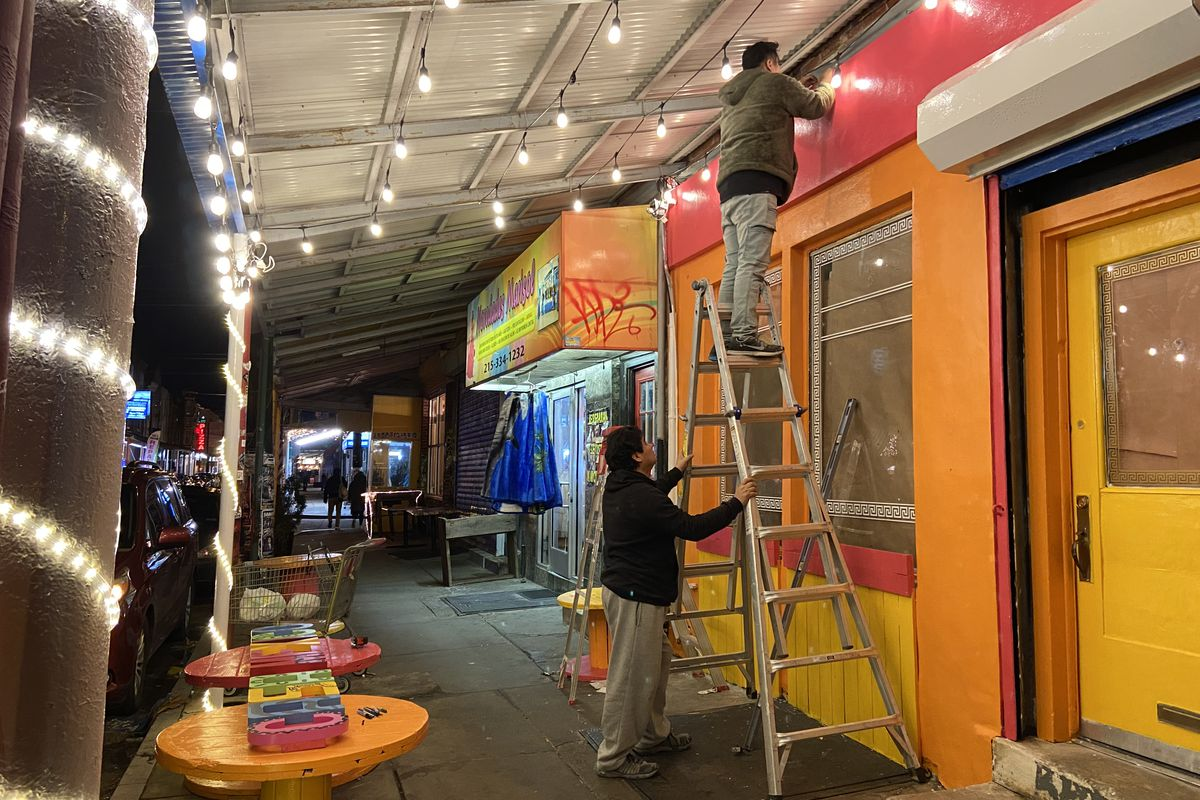 people hanging a sign at an orange and pink strorefront with string lights