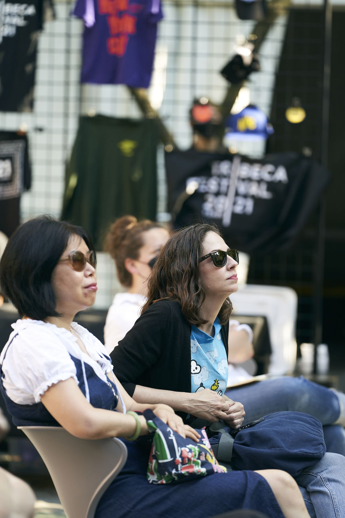 Two women in the foreground wearing sunglasses look up at the screen.