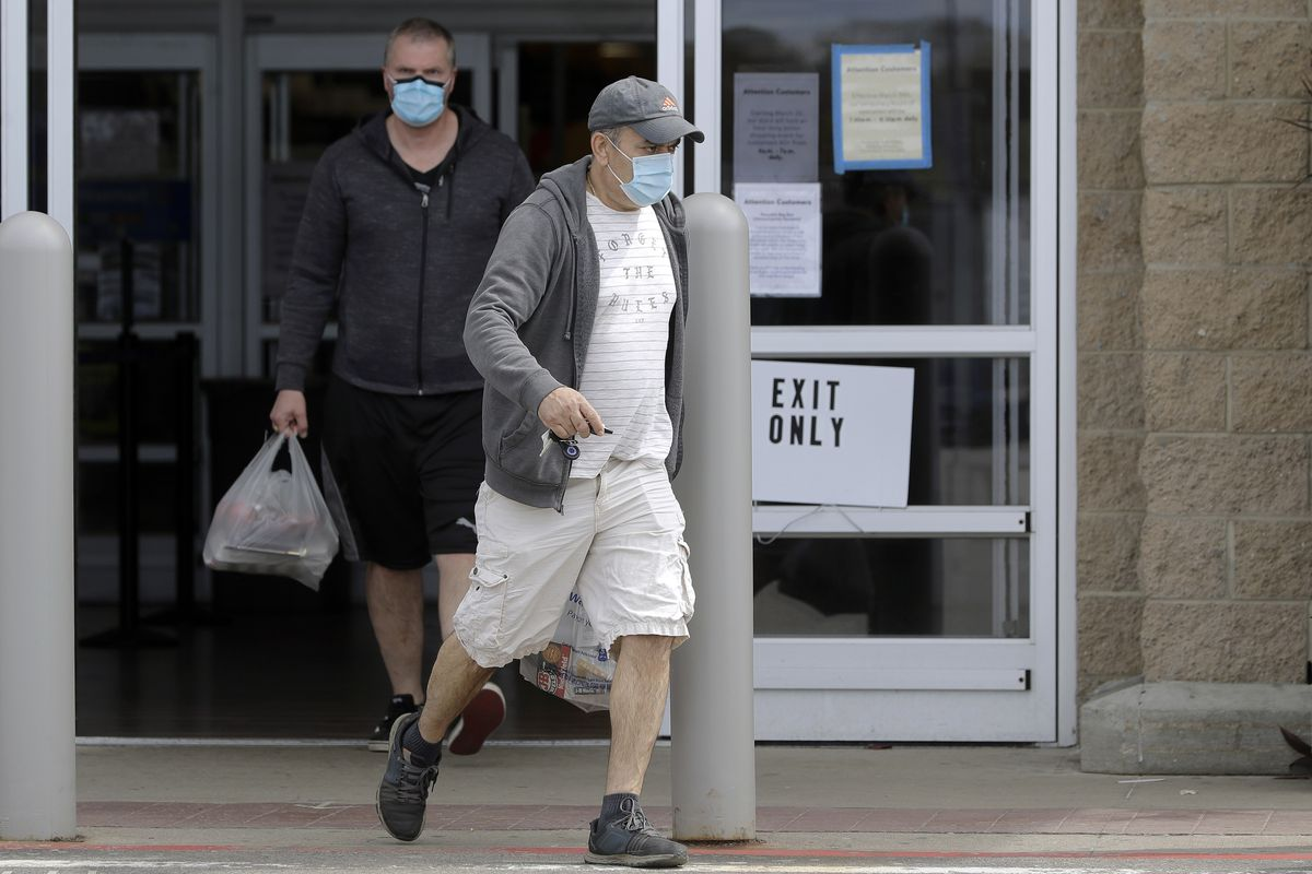 Men wearing protective masks during the coronavirus pandemic exit a Walmart, Wednesday, May 6, 2020, in Walpole, Mass. An executive order signed the previous week by Gov. Charlie Baker took effect Wednesday mandating the use of masks when individuals are not able to socially distance themselves from others.