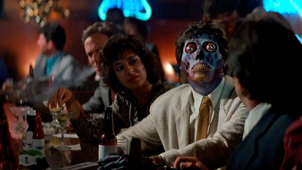 An alien peering up at a television in a bar in They Live (1988)