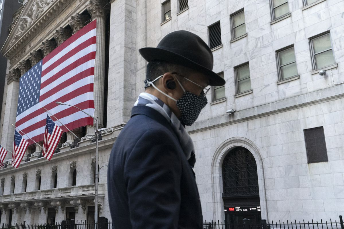 In this Nov. 16, 2020 file photo a man wearing a mask passes the New York Stock Exchange in New York. Stocks are moving modestly higher in early trading on Wall Street as investors cautiously welcome signs of calm in the bond market. The S&P 500 was up 0.4% early Thursday, March 4, 2021, and the yield on the 10-year Treasury held steady at 1.47%.