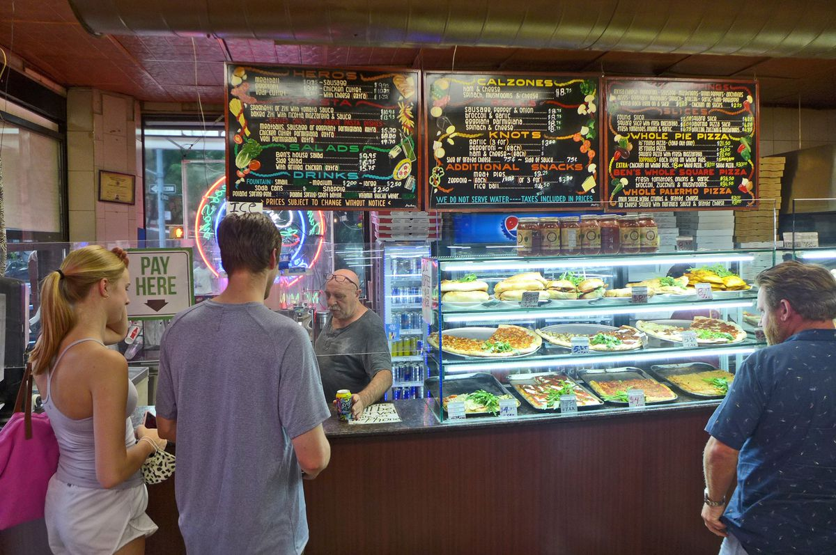 A man behind the counter and a few customers stand in front, with pizzas illuminated in a case at the right.