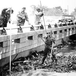 National Guardsmen and volunteers struggle to clear debris piling up at 39th South bridge over Jordan River. Sept. 28, 1982.