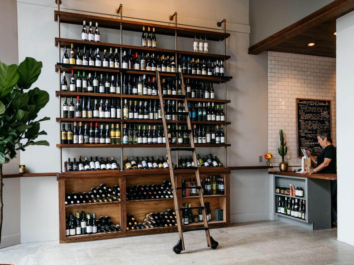 Wines arranged on a shelf inside the Royce. There's a wooden library ladder attached to reach the top shelves.
