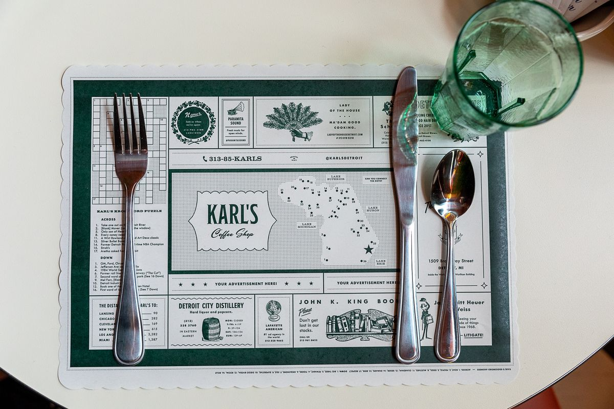 The Karl's placemat is green and white with a custom crossword puzzle and a connect the dots in the shape of Michigan. It's surrounded by advertisements for local businesses. The mat is covered with metal silverware and a clear green plastic cup.