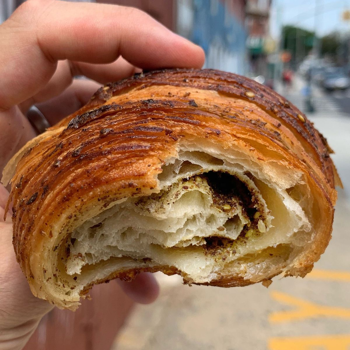 The cross-section of a croissant with a dark chocolate filling and flakey exterior