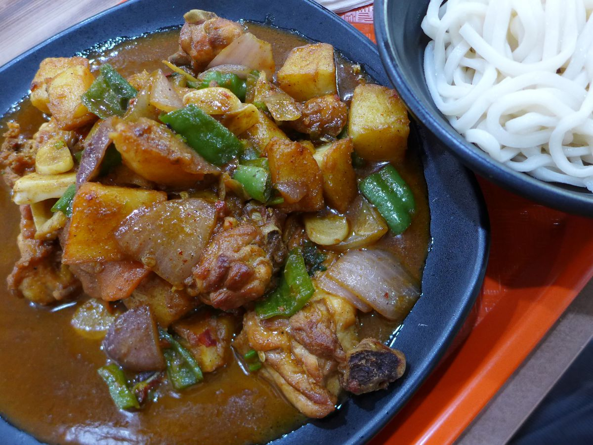 A bowl of chicken and potatoes in sauce with white noodles.