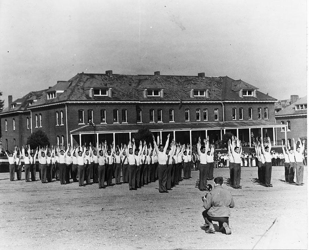A historic black and white photograph of officers working out in front of the Inn at the Presidio.