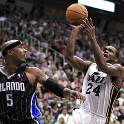 Utah Jazz's Paul Millsap, right, shoots past Orlando Magic's Quentin Richardson during the second half of an NBA basketball game in Salt Lake City, Saturday, April 21, 2012. The Jazz beat the Magic 117-107 in overtime. (AP photo/George Frey)