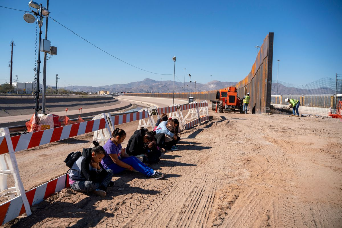 Salvadoran migrants wait for a transport to arrive after turning themselves into US Border Patrol by border fence under construction in El Paso, Texas on March 19, 2019.