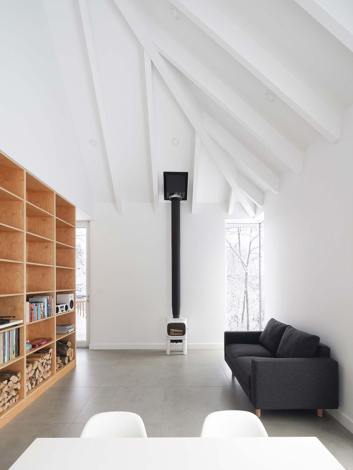 Living room with high ceilings and wooden shelf on one wall.