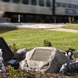 An outbound Metra train travels past a memorial at Algonquin Road and Northwest Highway in Fox River Grove, Wednesday afternoon, Oct. 21, 2020. On Oct. 25, 1995, inbound Metra train No. 624 crashed into a school bus at that intersection, killing seven teenagers and injuring the bus driver and 24 passengers.