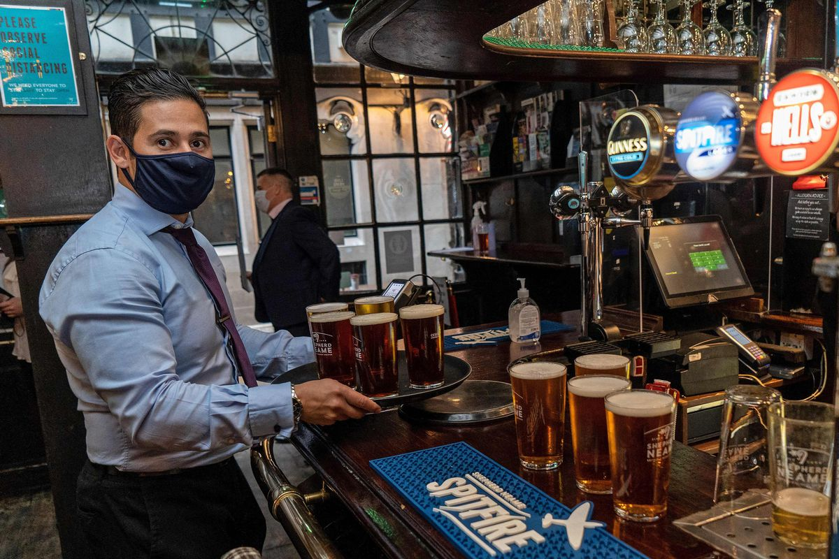 A bartender wearing a face covering serves customers their pints of beer inside a re-opened pub in London last month.
