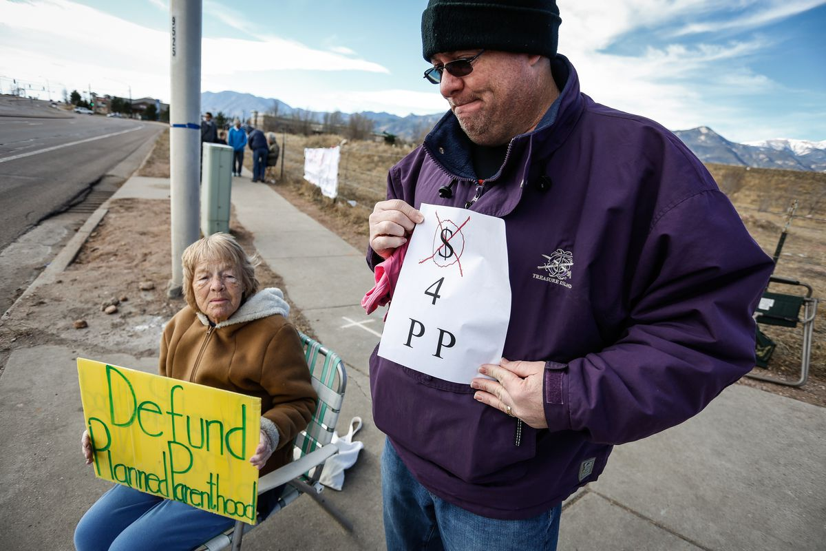 "Protesters outside of the Colorado Springs Westside Health Center February 11, 2017 in Colorado Springs, Colorado, hold signs reading ""Defund Planned Parenthood"" and ""No $ 4 P P."""
