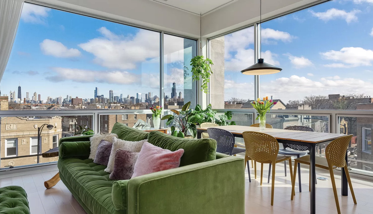 A living room with large floor-to-ceiling windows. There is a green velvet couch and a dining room table with six chairs.